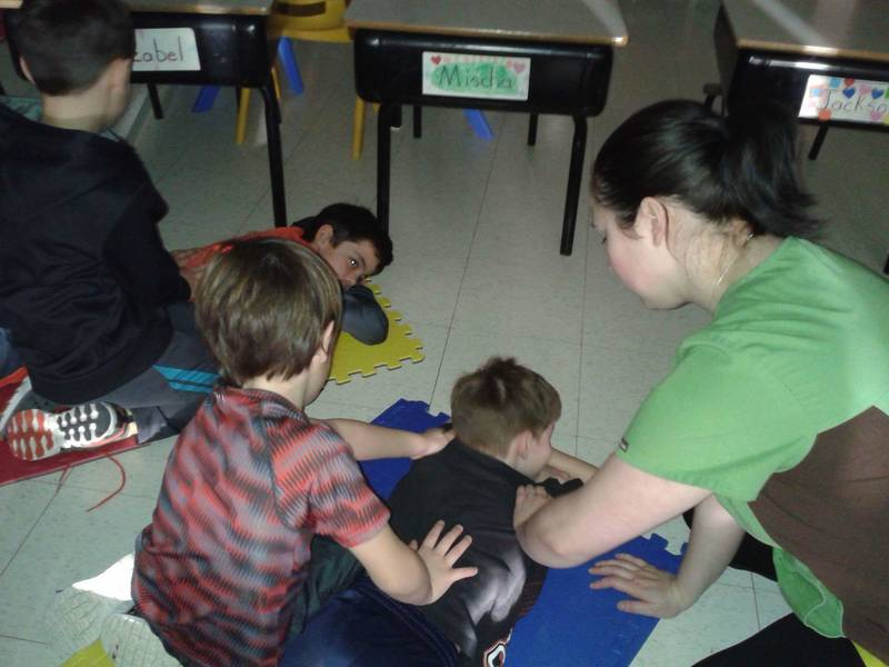 Samantha showing some grade 2 students how to give each other a massage!